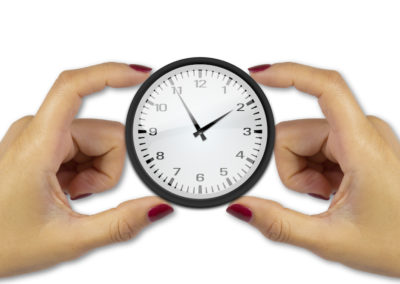 Two female hands holding a clock on white background keep track of time concept